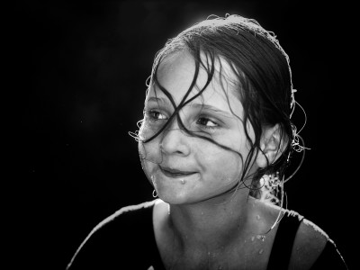 A girl playing in hose in front yard by Sydney Photographer- CIndy Cavanagh